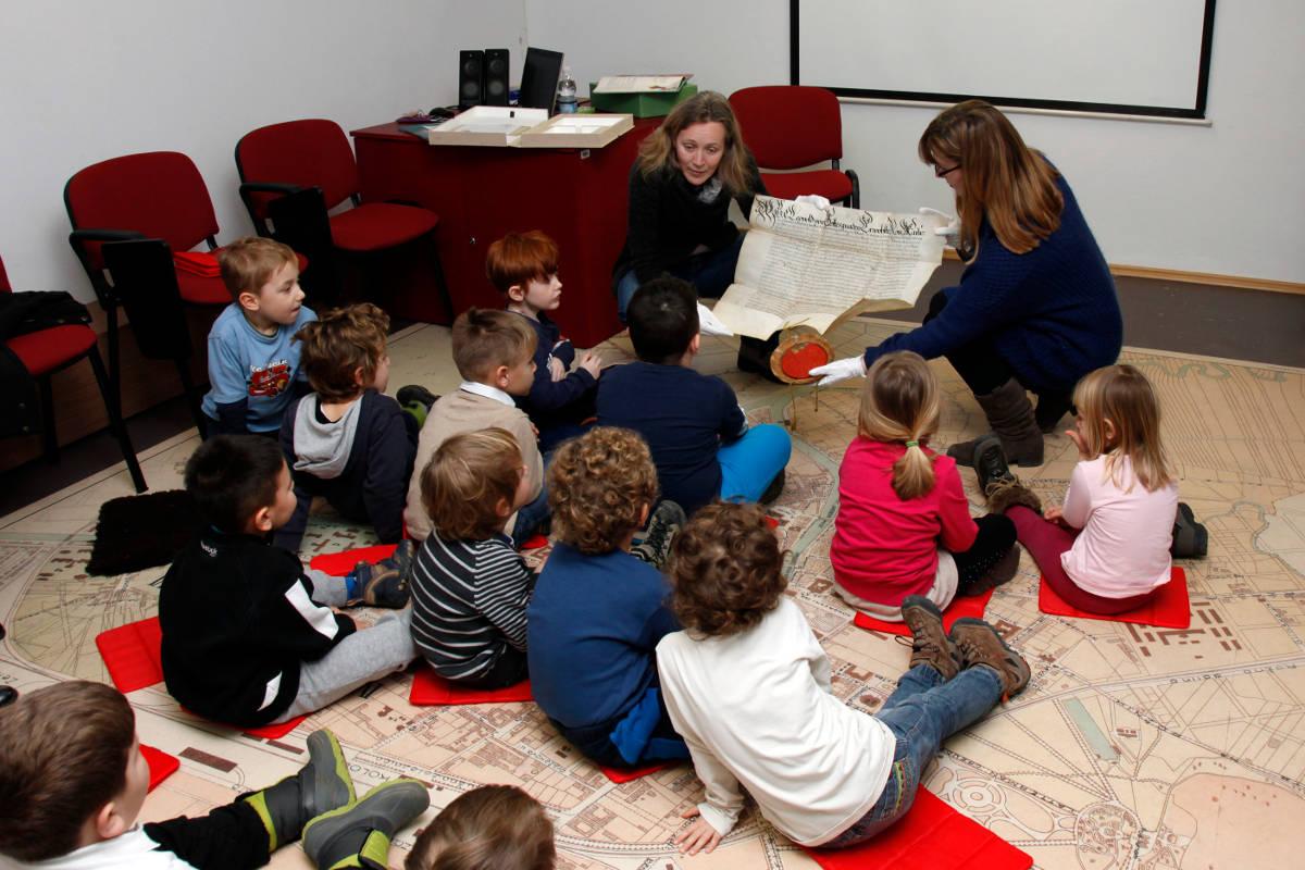Sedeča skupina otrok pri predstaviti listine s pečatom