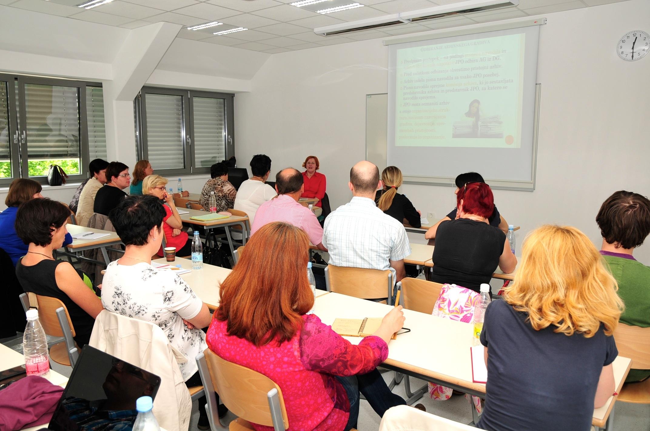 Udeleženci seminarja za preizkus strokovne usposobljenosti gledajo predstavitveni pano